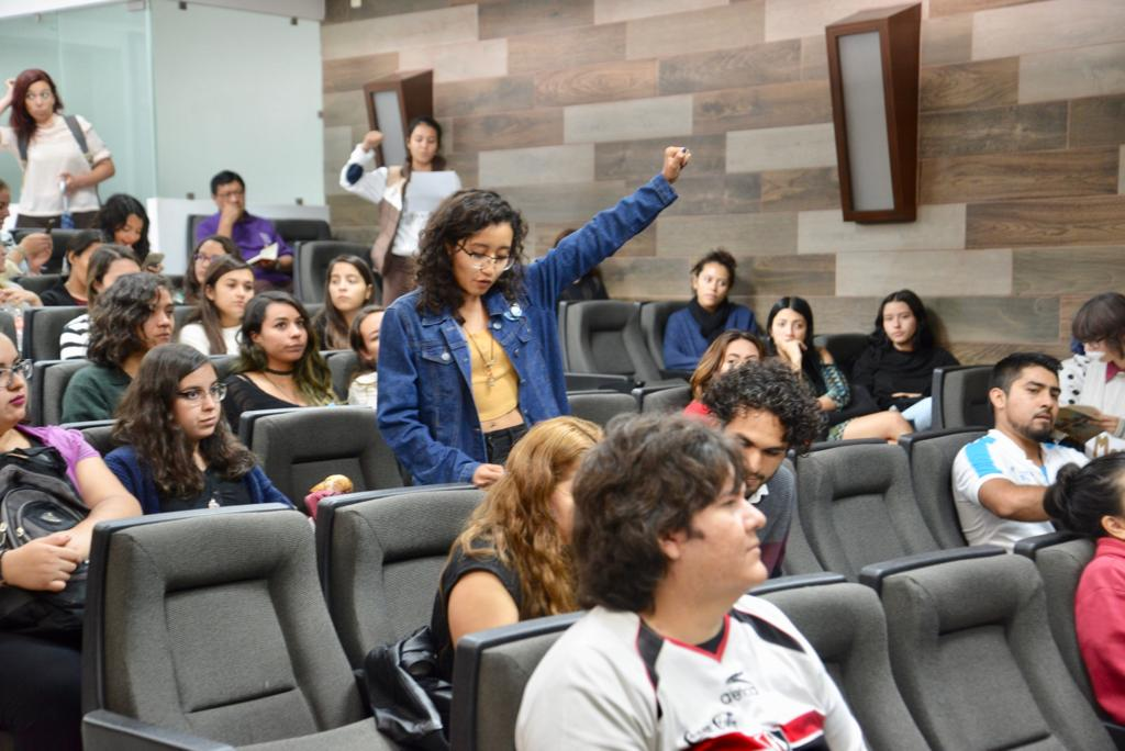Asistente al Panel, alumna de pie alzando el brazo izquierdo con la mano empuñada al leer su extracto del poema colectivo
