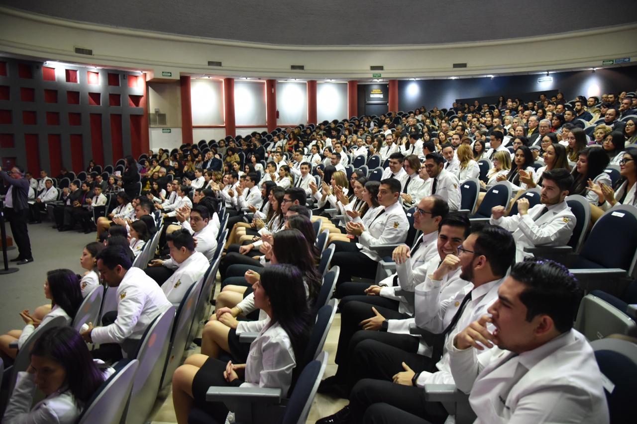 Alumnos graduados con bata blanca en sus butacas