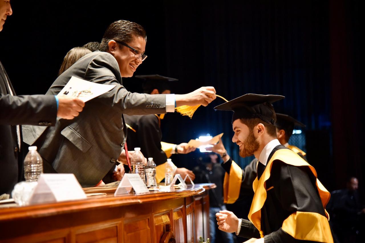 Rector del CUCS cambiando la mota del birrete a alumno graduado