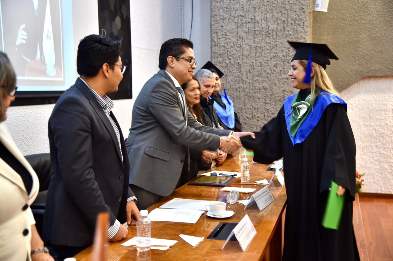 Rector entregando constancia a graduada saludándola de mano