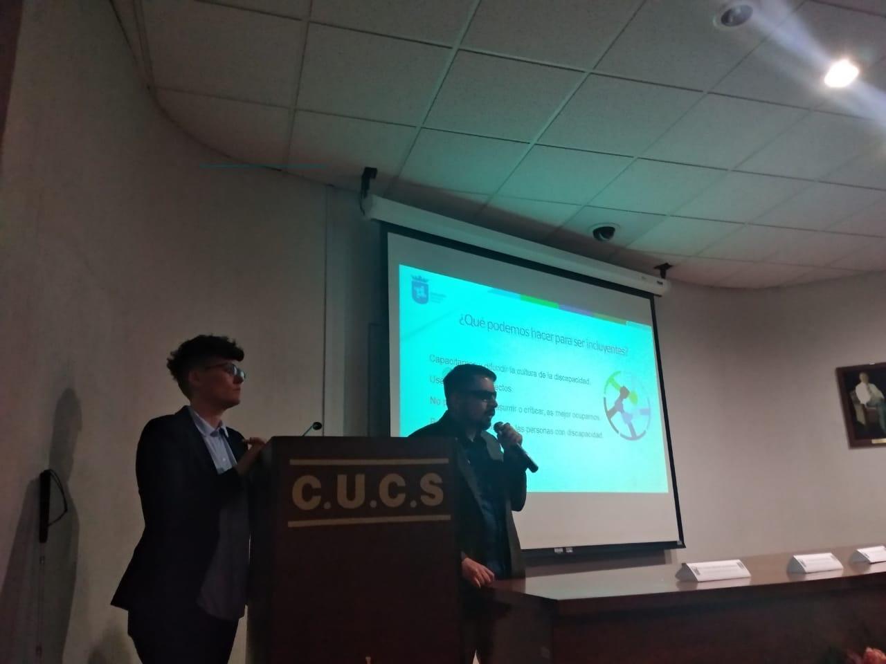 Ponente impartiendo conferencia, al fondo una diapositiva