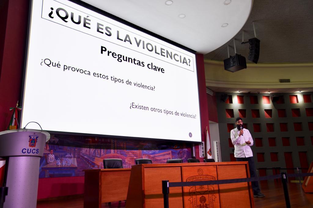 """Ponente dictando conferencia, al fondo una diapositiva con el título """"¿Qué es la violencia""""?"""