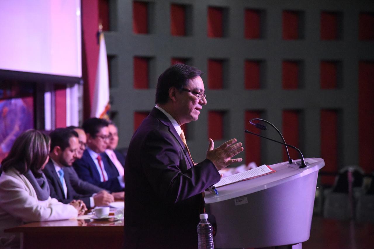 Dr. Pedro Farfán Flores al micrófono en el pódium