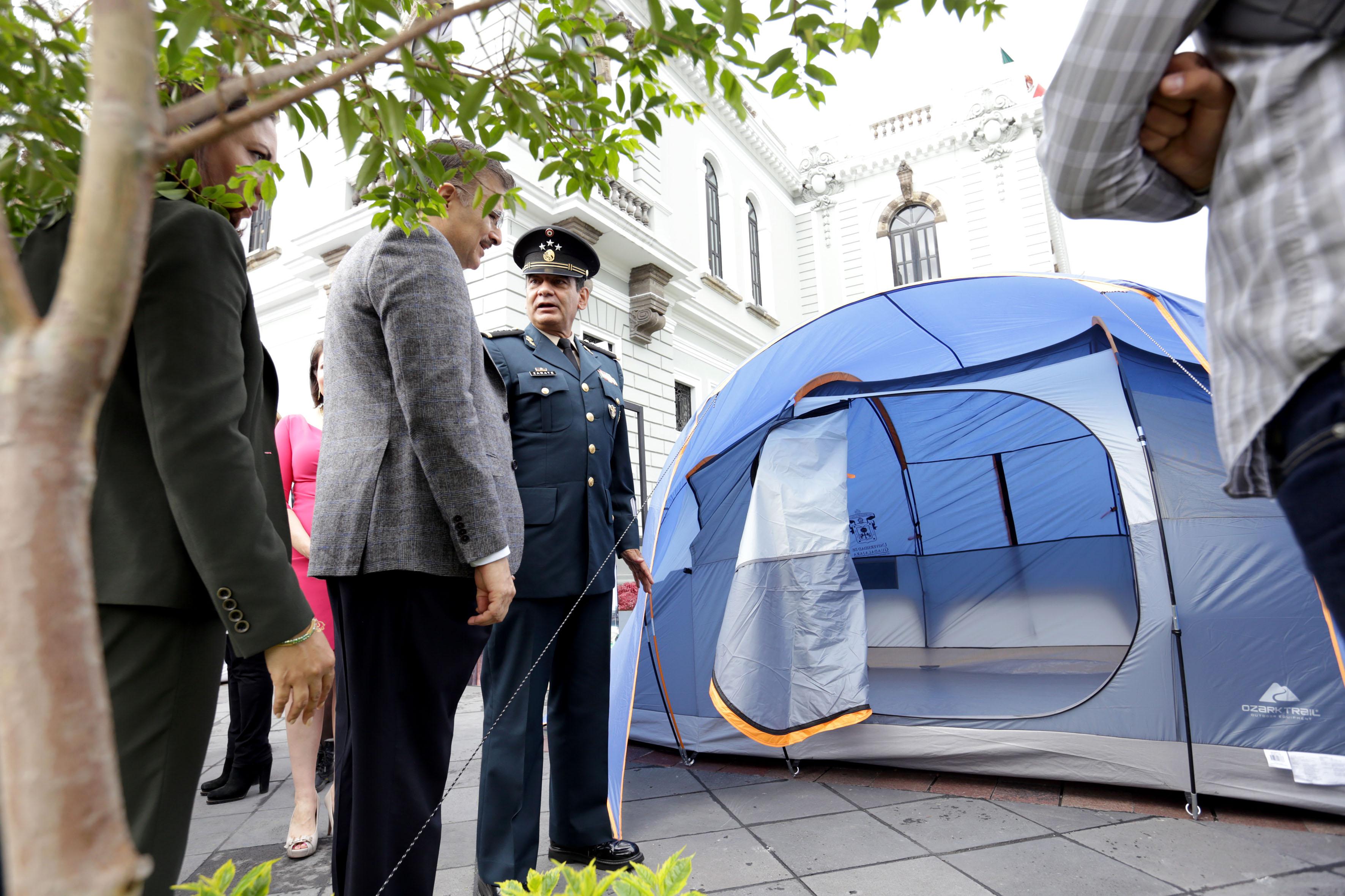 El Rector General y el General de la V Región Mililtar recorren por fuera una de las casas de campaña