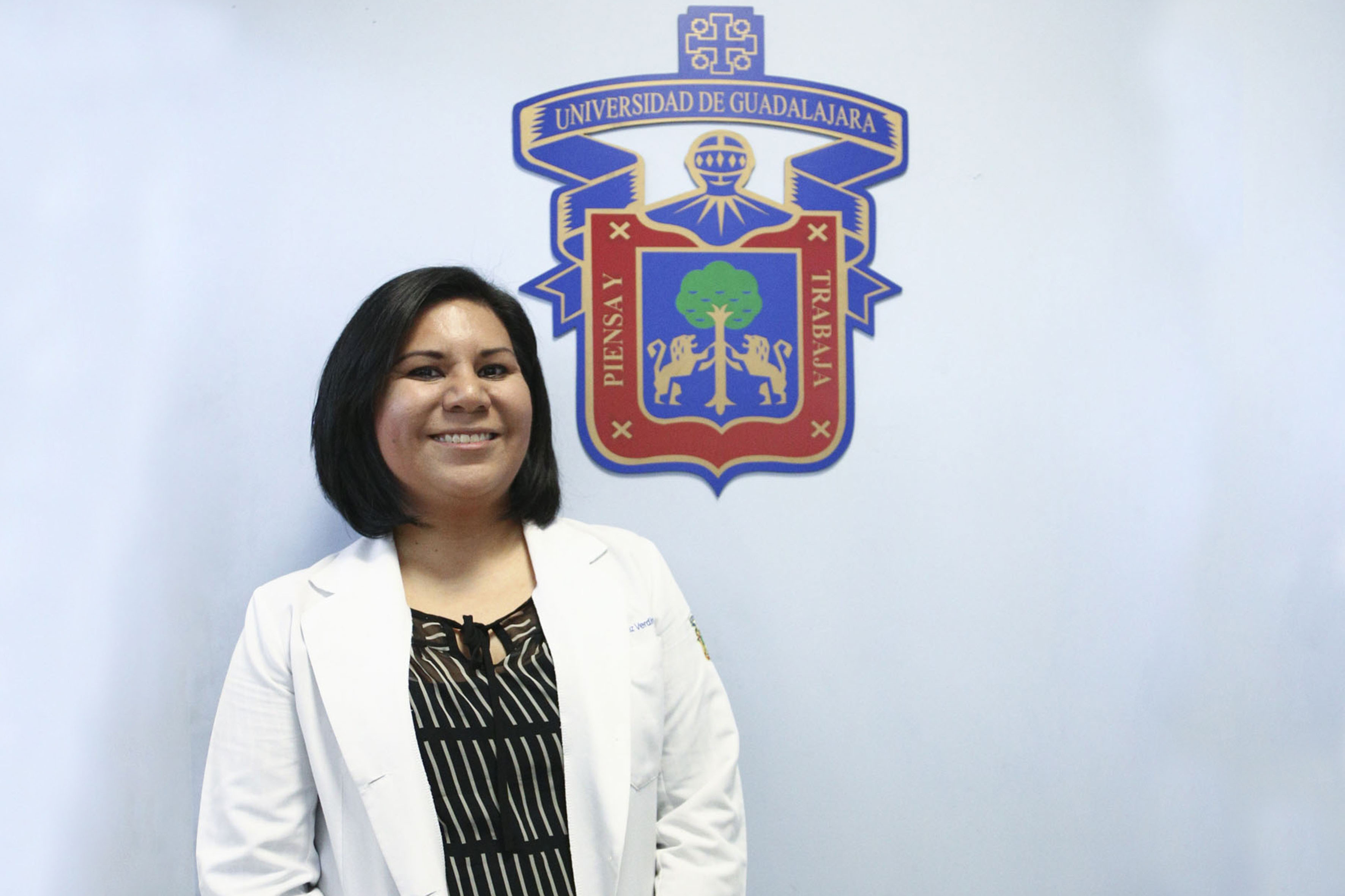 Dra. Sandra López Verdín posando junto al escudo de la UdeG