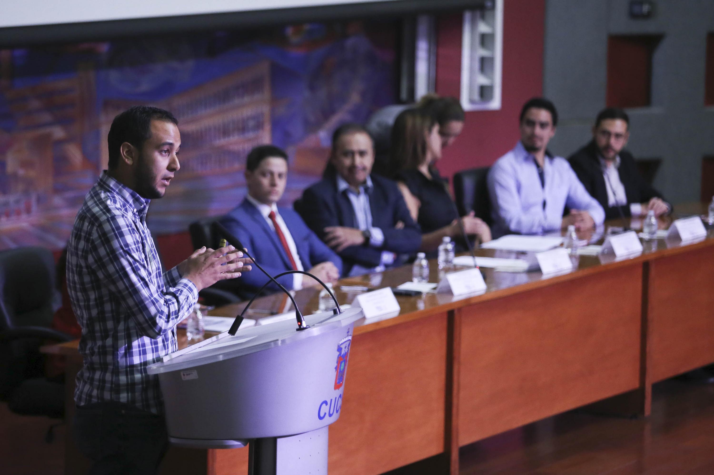Presidente FEU exponiendo en podium y al fondo miembros del presídium