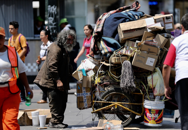 Indigente adulto mayor en la calle con carro lleno de objetos en desuso
