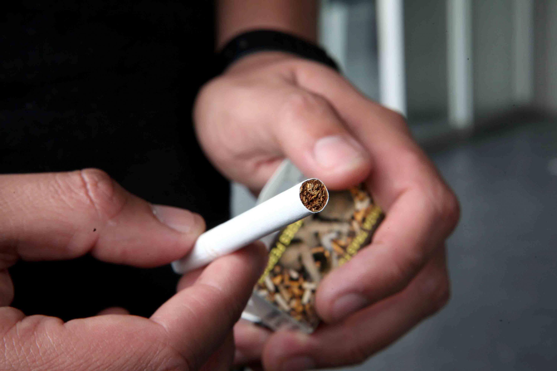 Cigarro en las manos de un joven