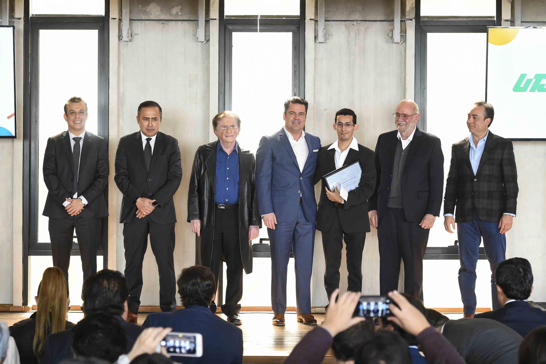 Funcionarios de Gobierno posando en la foto con el alumno de Medicina ganador del premio