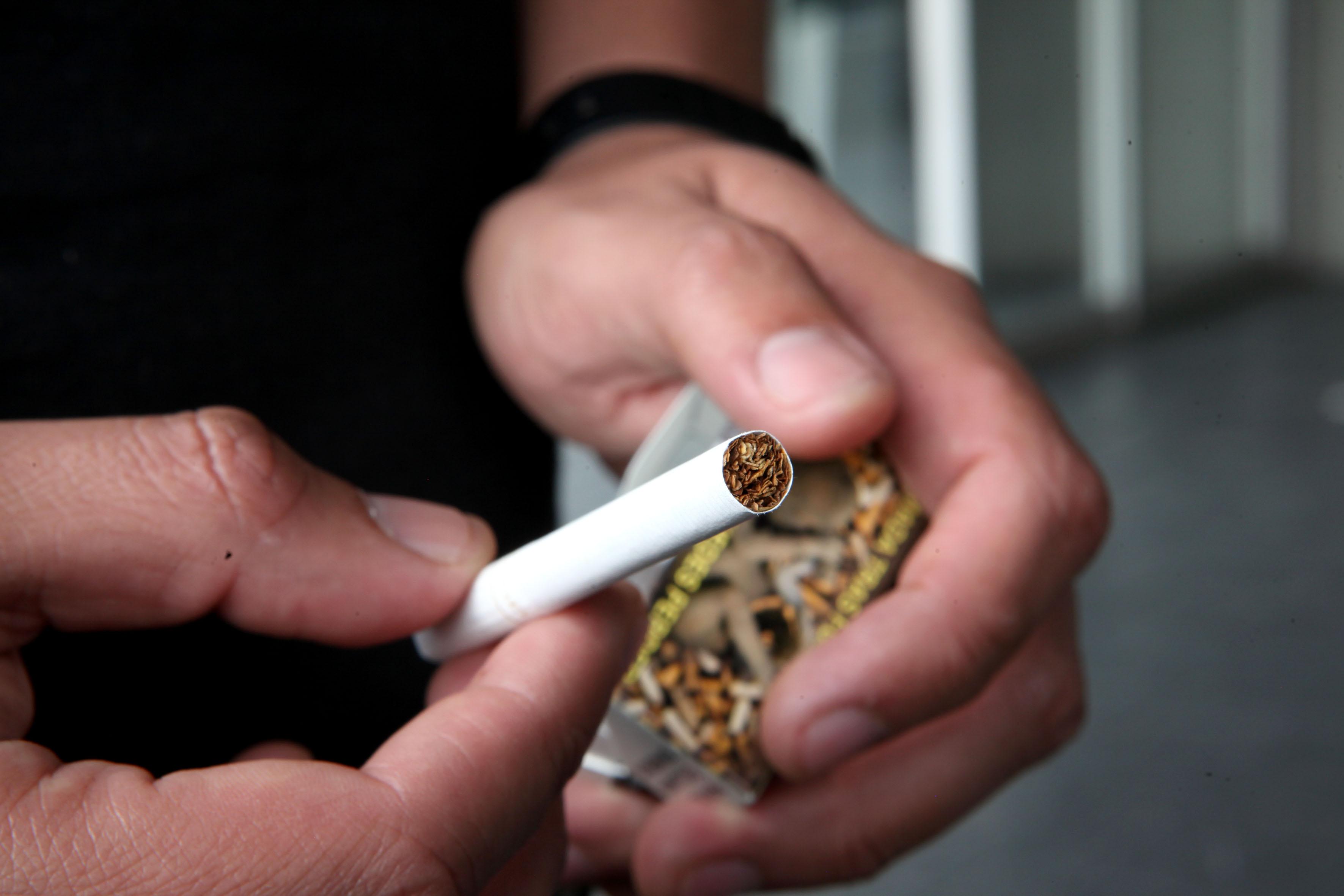 Un cigarro en las manos de un joven