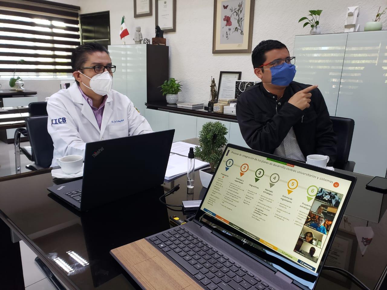 Rector analizando información en la pantalla de su oficina junto con el coordinador de Planeación