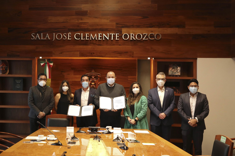 Funcionarios universitarios y directivos de la empresa exhiben el convenio firmado y posan para la foto