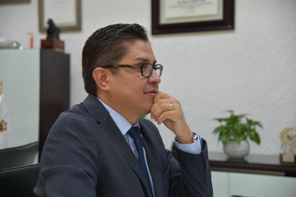 Rector presidiendo la sesion desde su oficina, está sentado frente a la pantalla