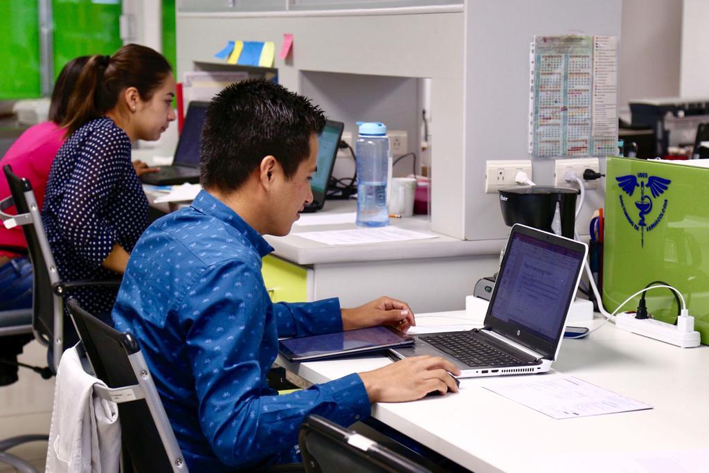 Alumnos del CUCS frente a una laptop