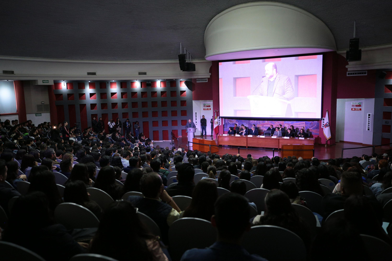 Vista general del auditorio a lleno total , al fondo el rector general dando mensaje desde el podium