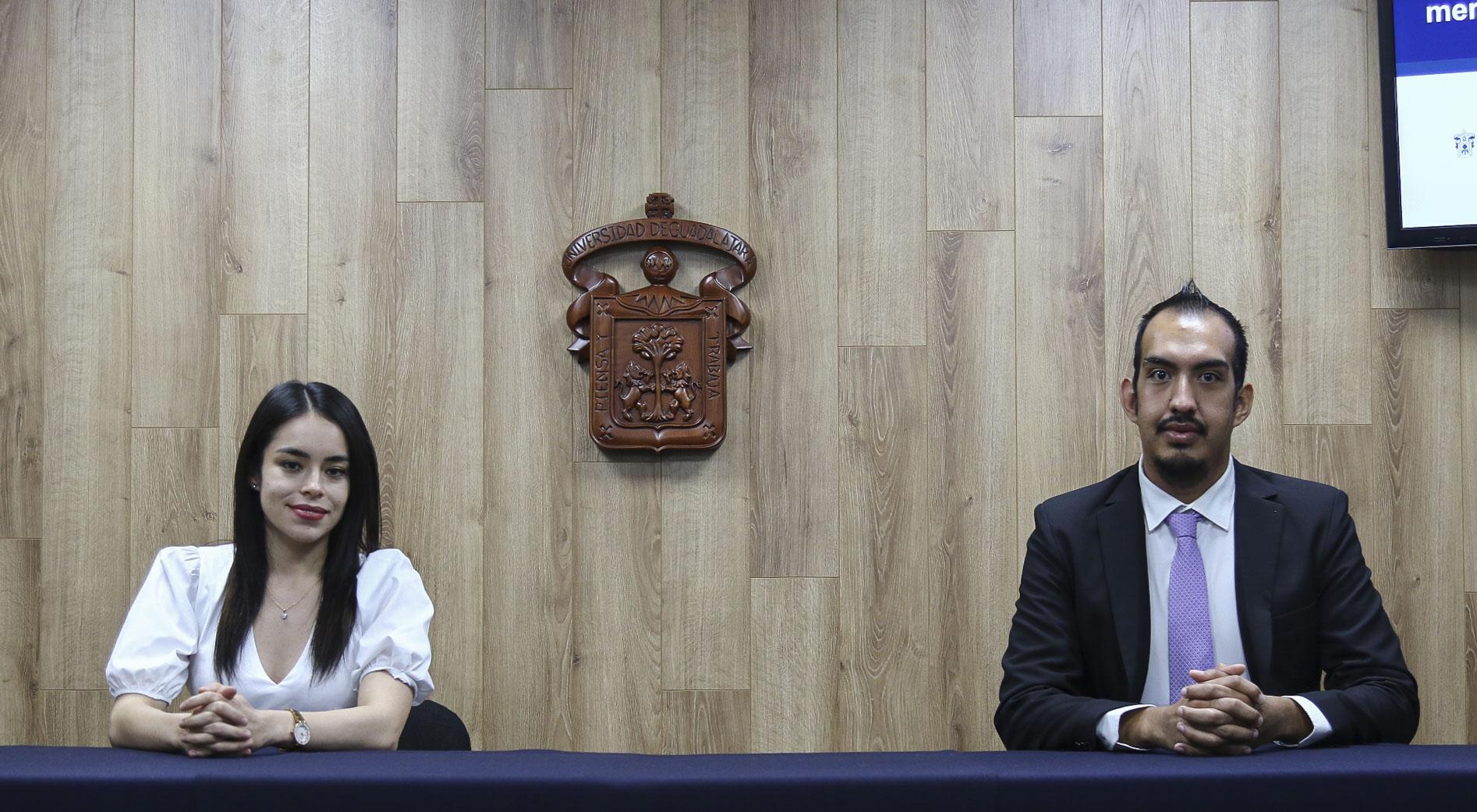 Foto de los dos premiados de CUCS, al fondo el escudo de la UdeG