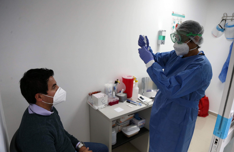 Personal de salud prepara el isopo frente al paciente