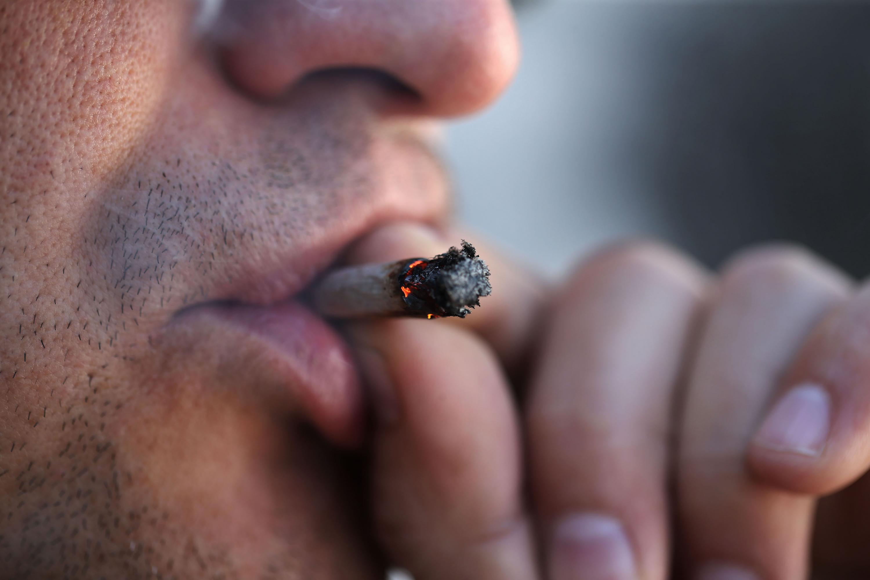 Rosrro de un varón fumando un cigarrillo de marihuana