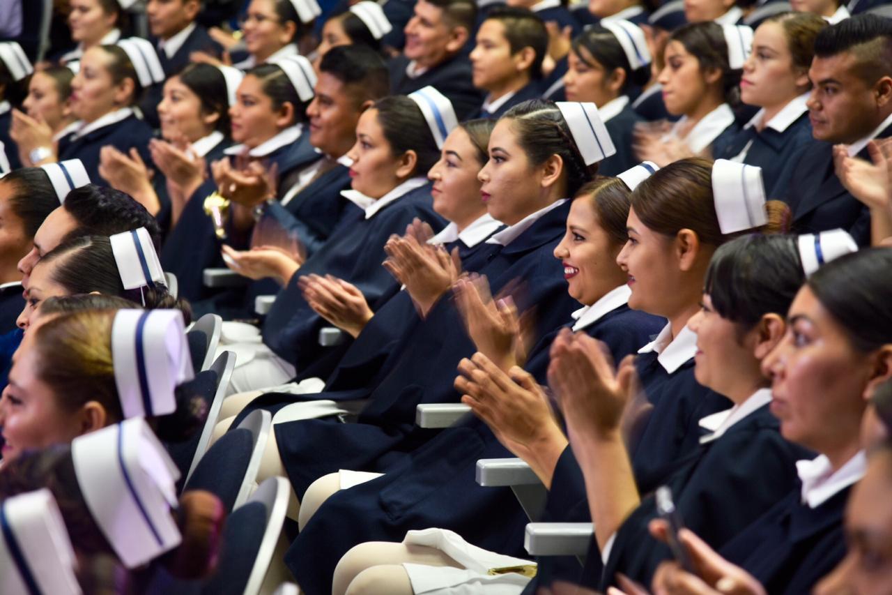 Enfermeras y enfermeros graduados en sus butacas aplaudiendo