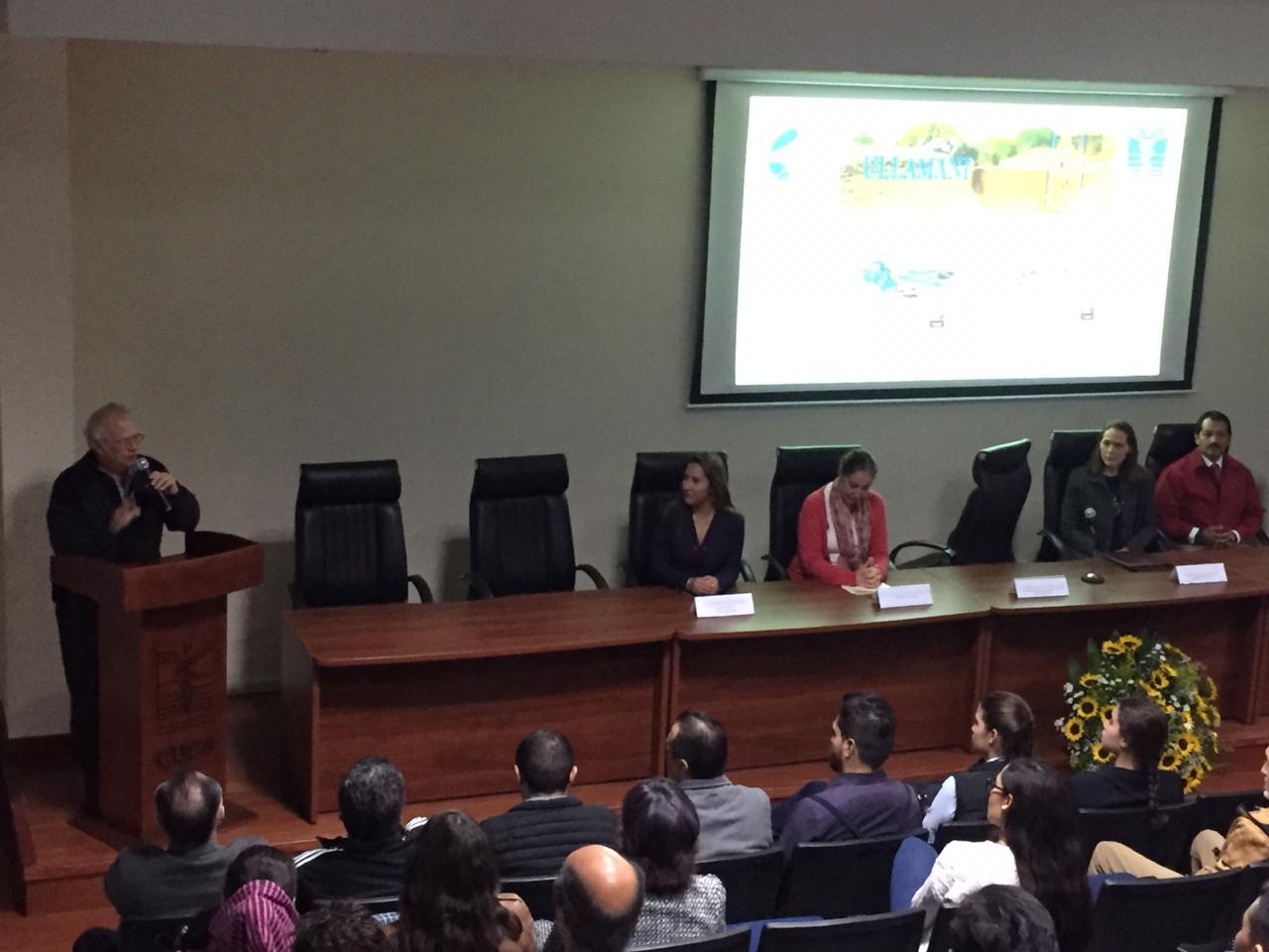 Dr. Alfredo Celis al micrófono en el podio, a su lado los miembros del presídium