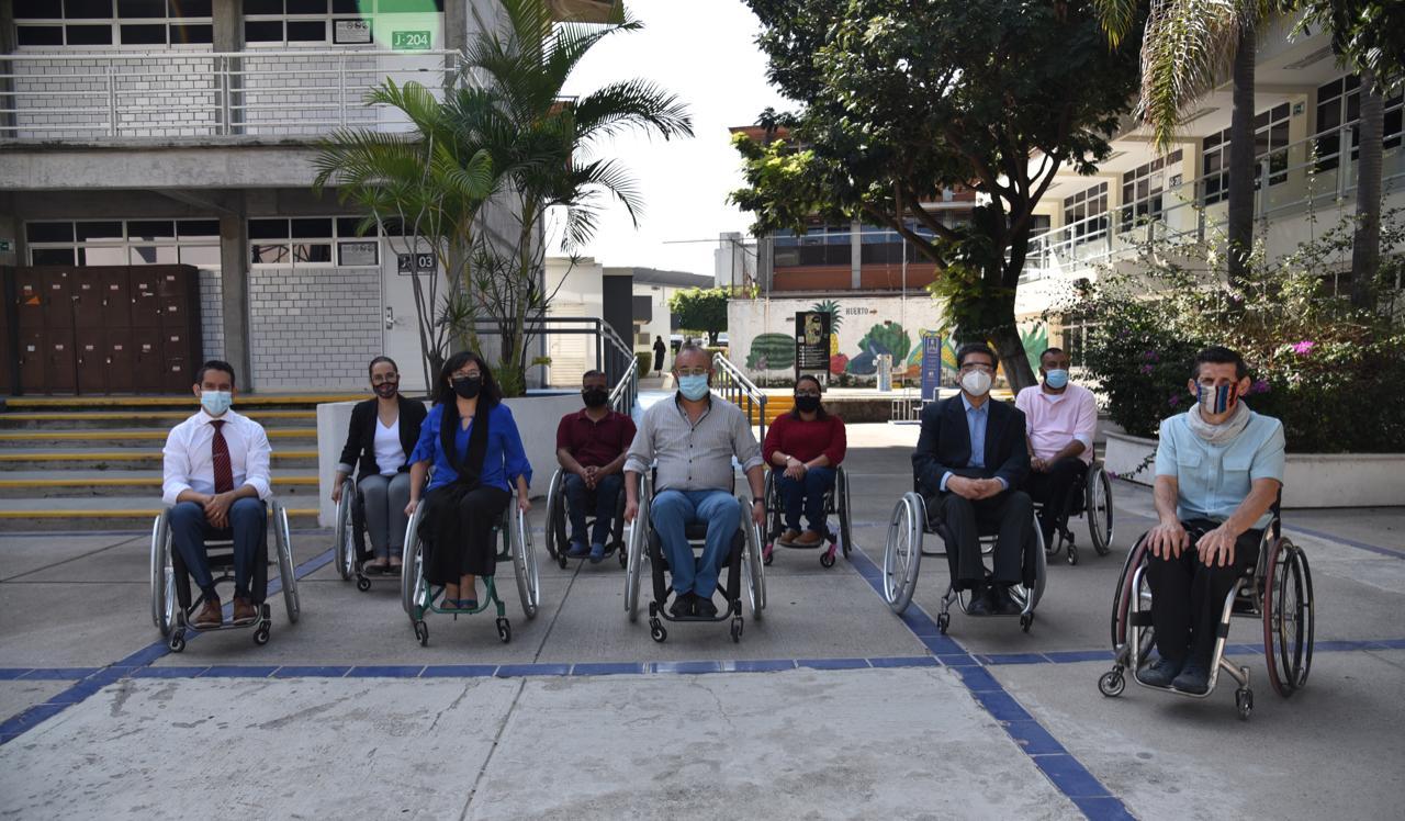 Académicos de CUCS sentados en silla de ruedas posando para la foto