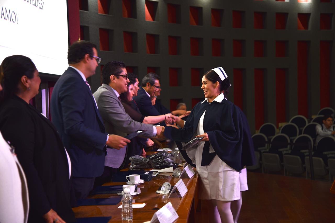 Enfermera graduada recibiendo acta de manos del rector del CUCS