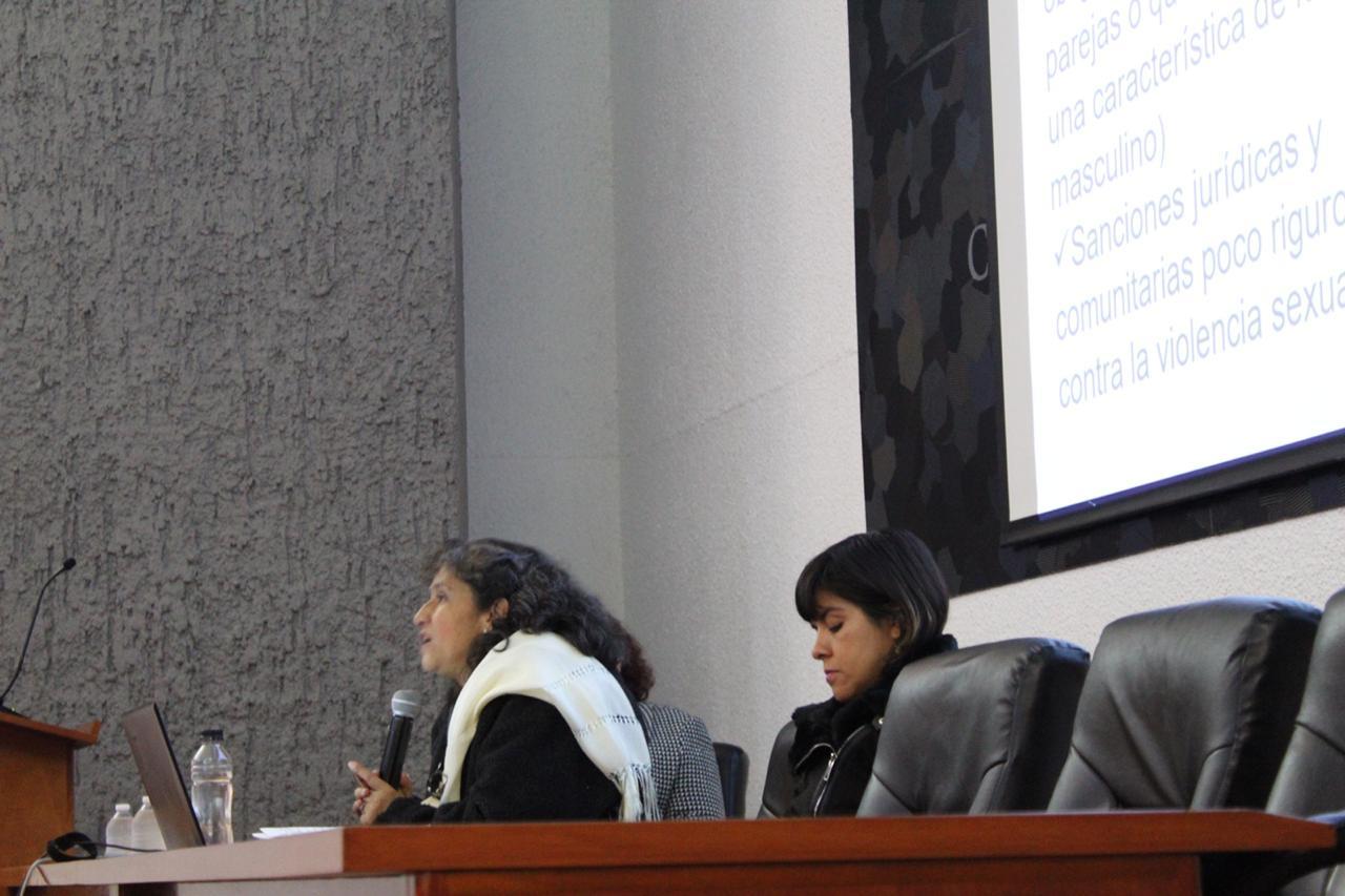 Especialista impartiendo conferencia, a su lado en la mesa del presídium la responsable de la Defensoría de Derechos Universitarios del CUCS