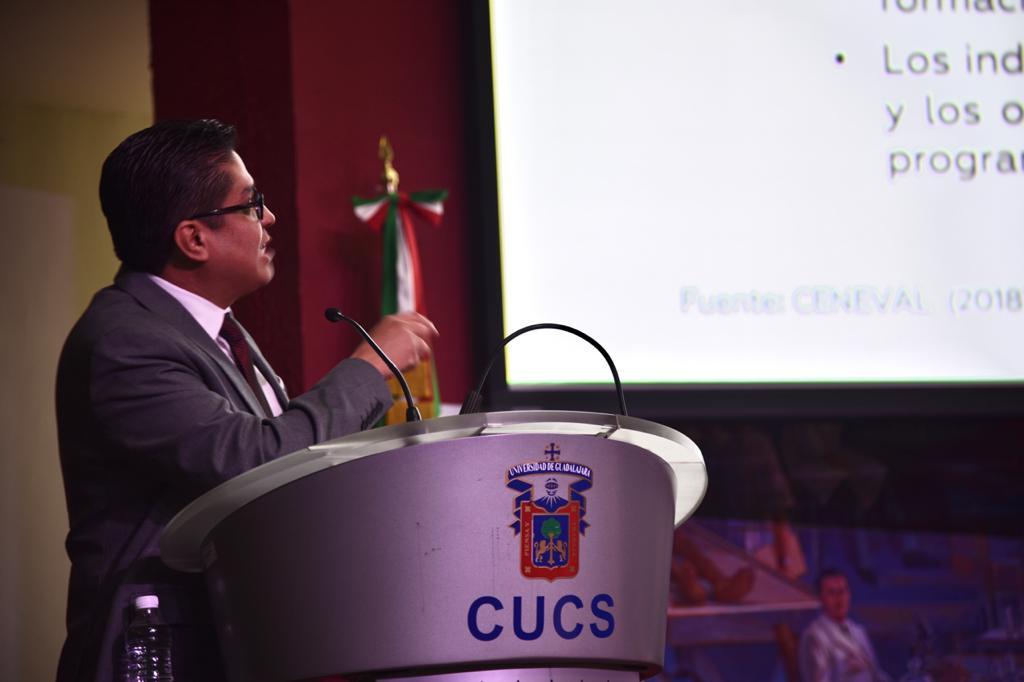 Rector del CUCS mostrando diapositiva con resultados del EGEL