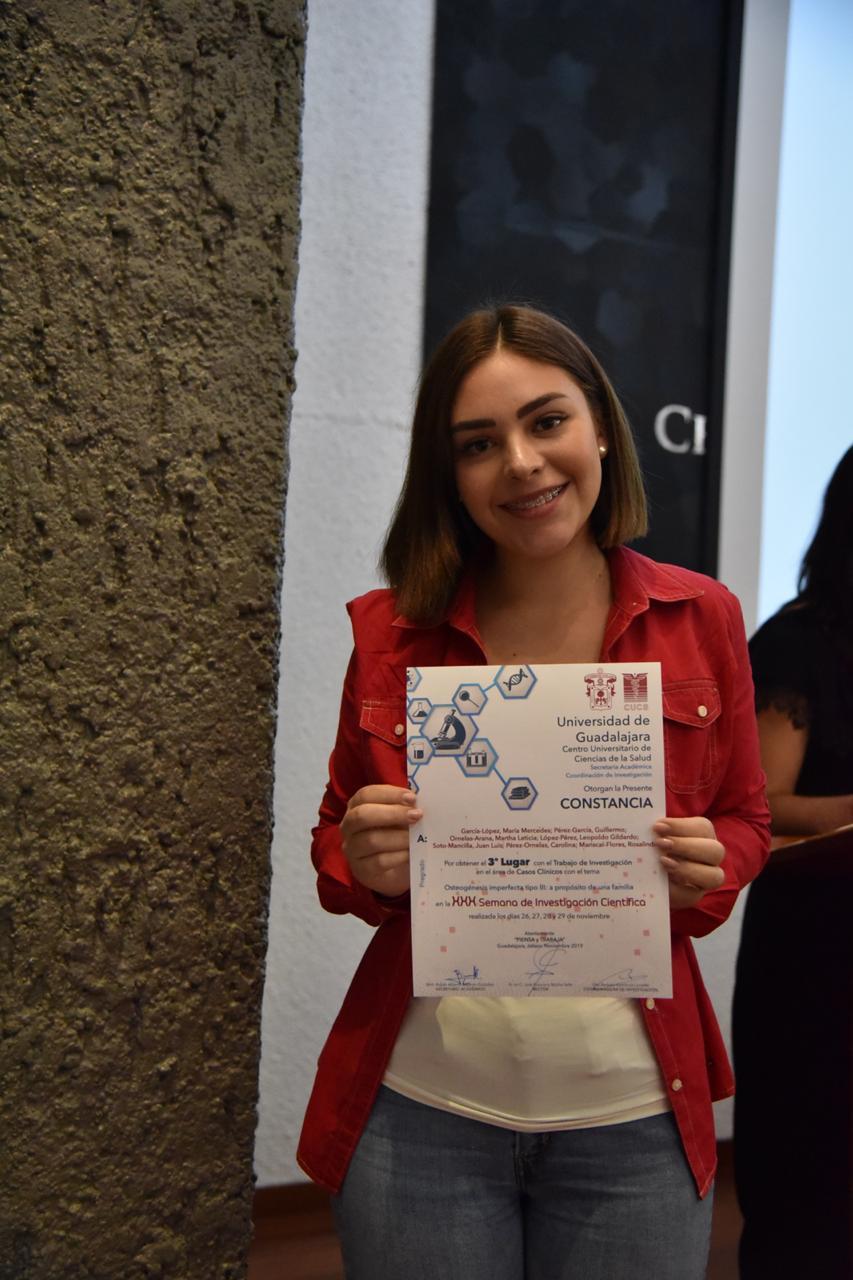 Alumna ganadora exhibiendo su reconocimiento