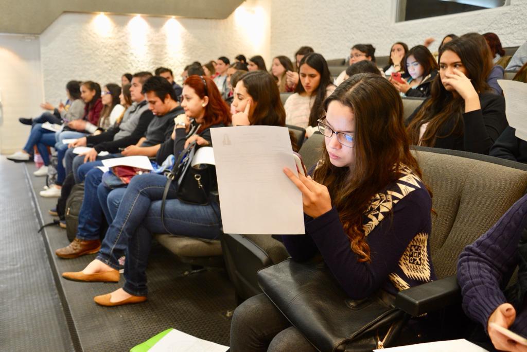 Alumna del CUCS revisando documentos en un auditorio