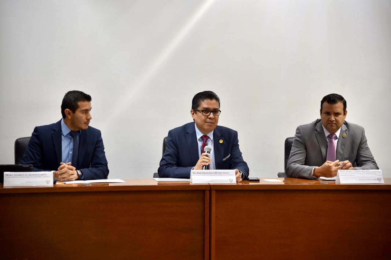 Miembros del presídium, rector al centro haciendo uso del micrófono para tomar protesta a miembros del Comité