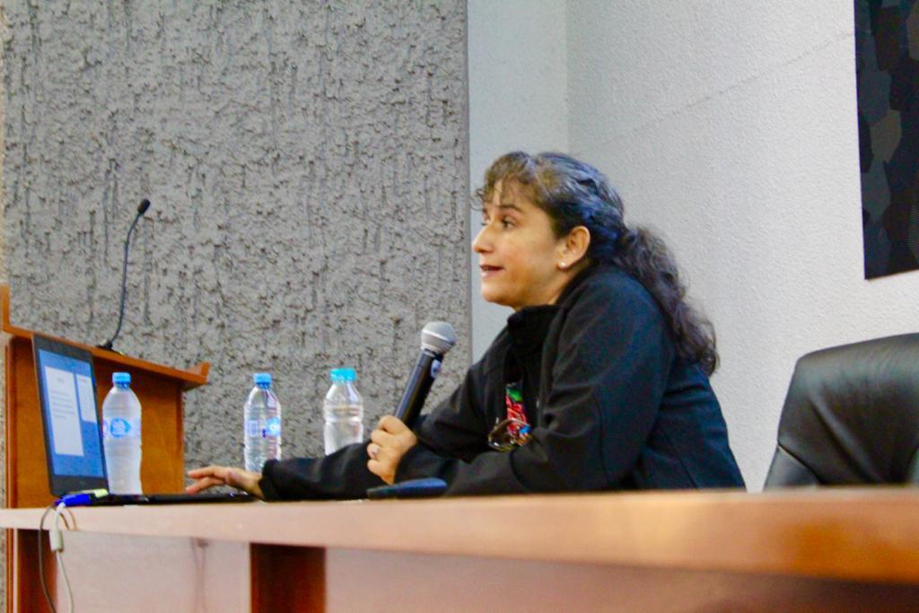 Conferencista al micrófono desde la mesa del presídium
