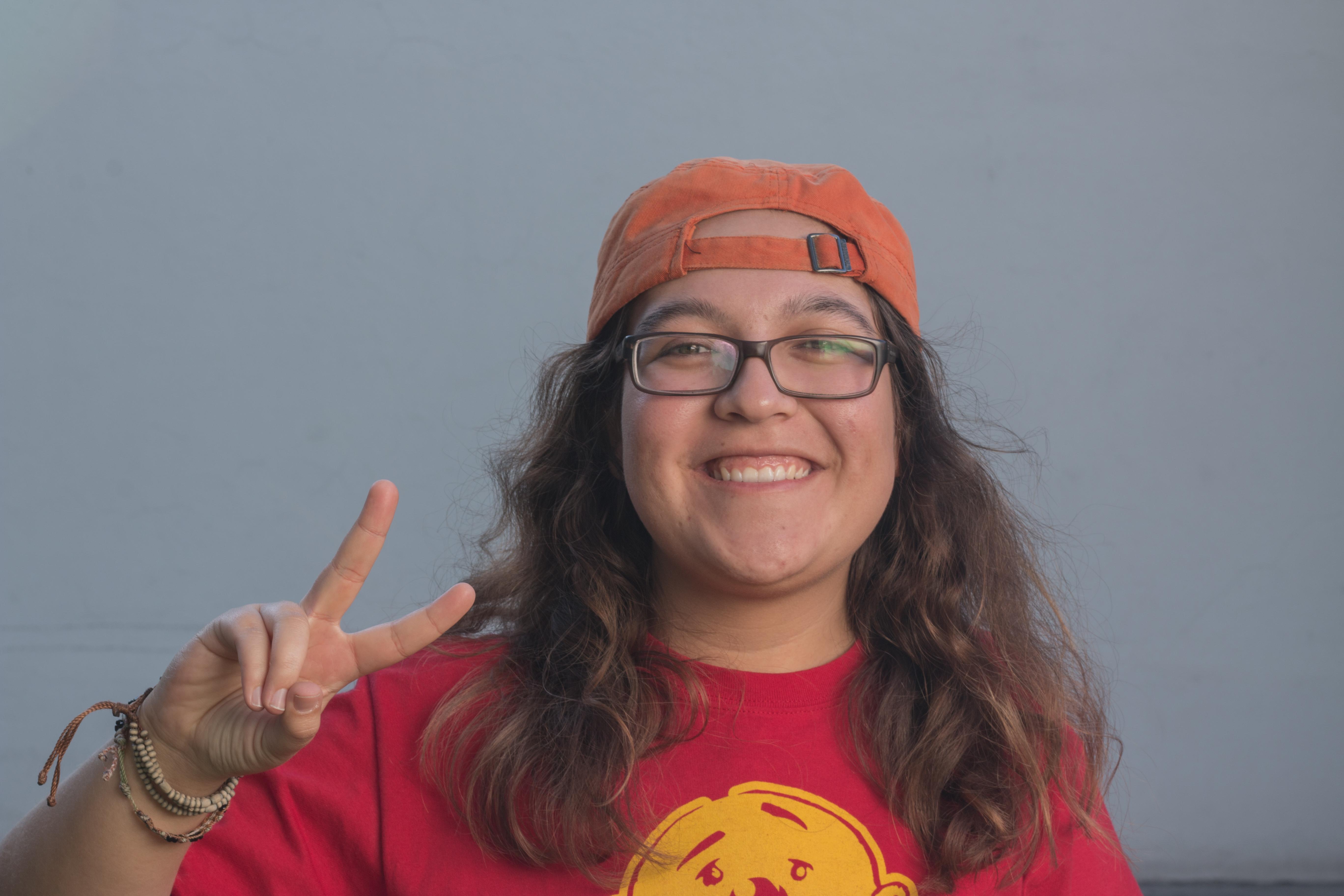 """María Adriana Espinosa muy sonriente haciendo el signo de """"amor y paz"""""""