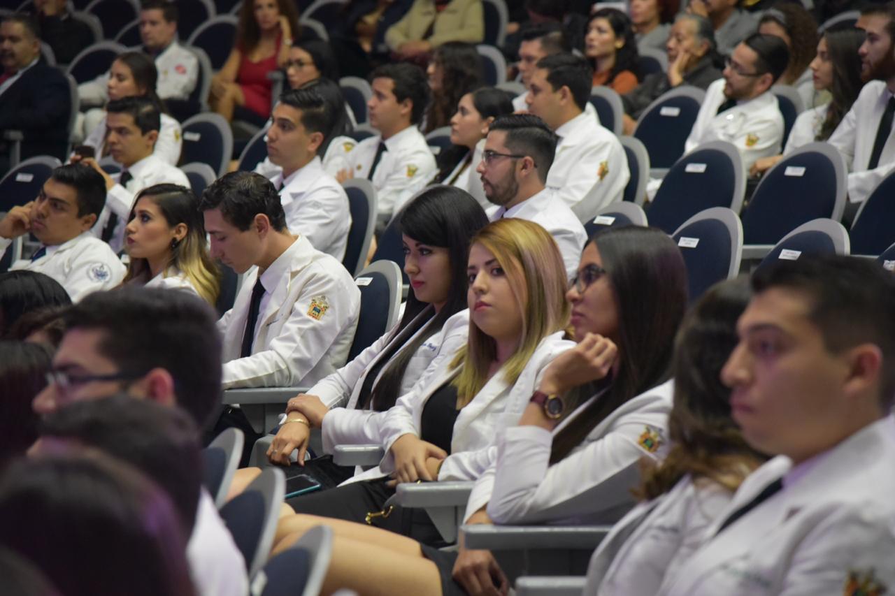 toma cerrada de alumnos graduados con su bata blanca
