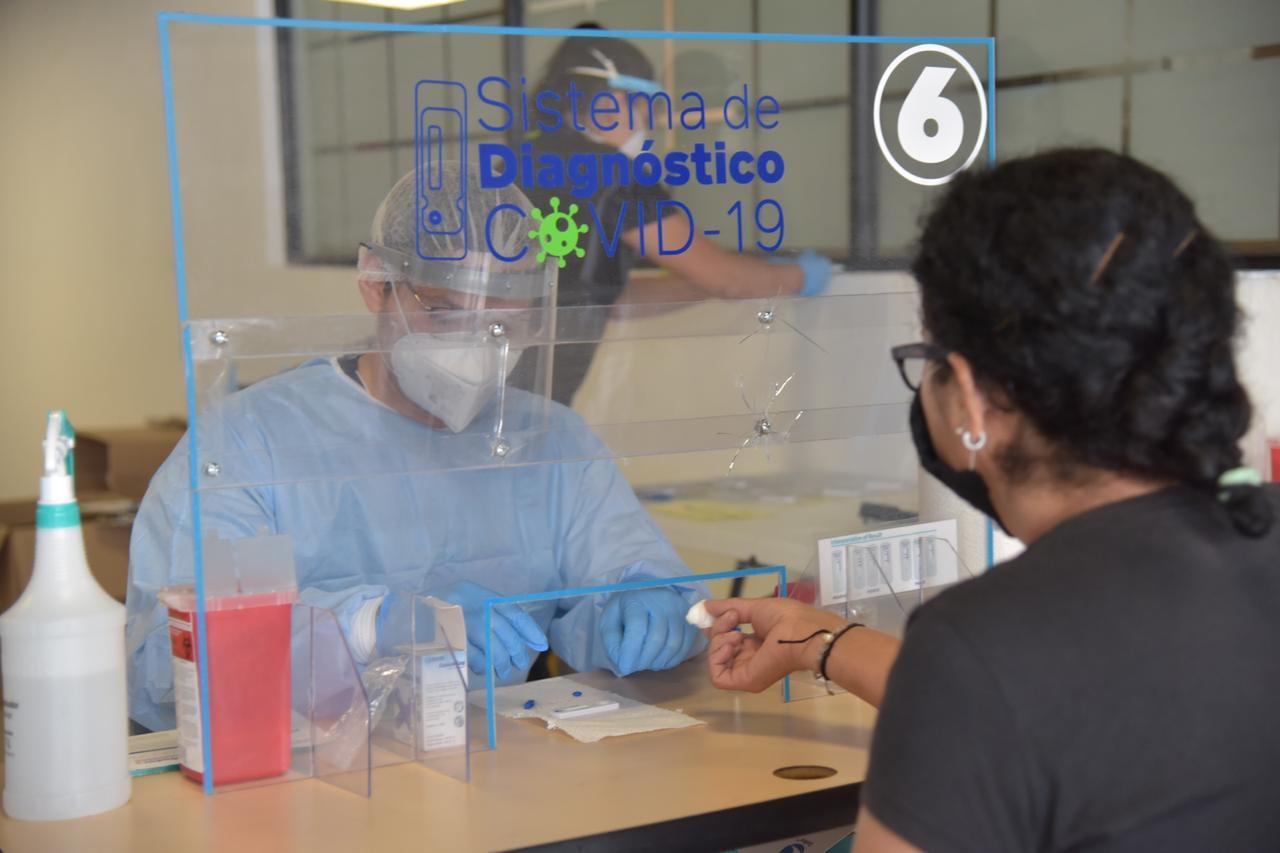 Módulo de pruebas rápidas, médico y paciente tras una ventanilla de plásico