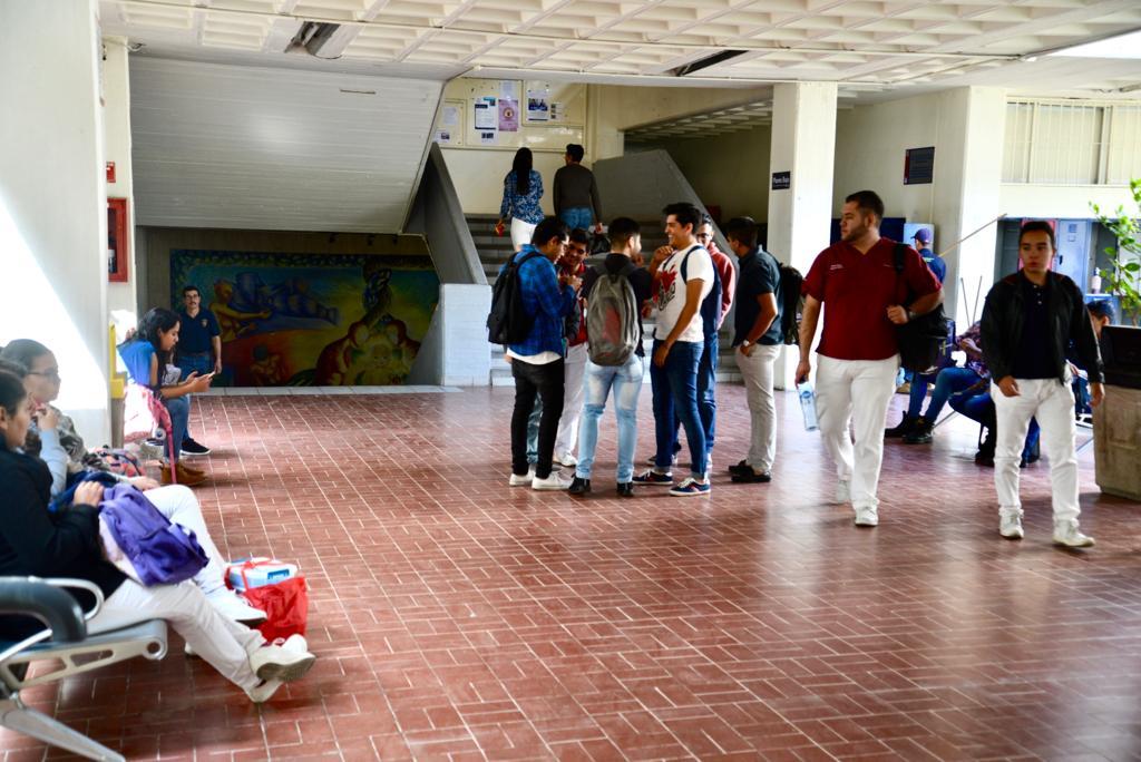 Alumnos del CUCS desplazándose con prisa por los pasillos del centro universitario