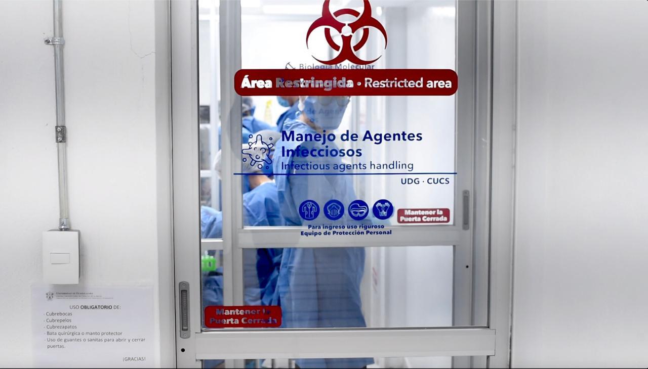 Puerta de ingreso con letrero al área de Manejo de Agentes Infecciosos