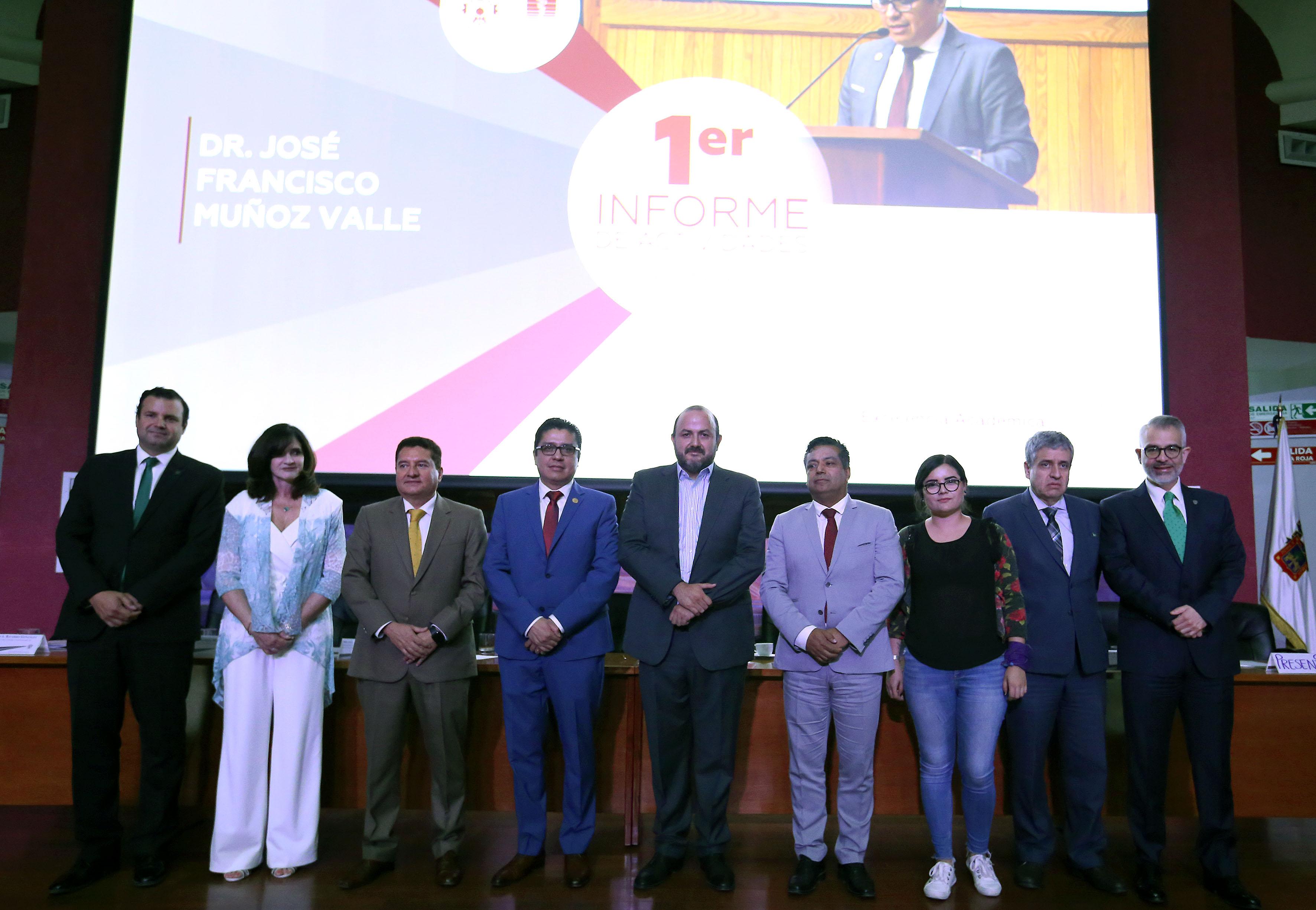 Fotografía grupal de miembros del presídium con el Rector General al final del informe