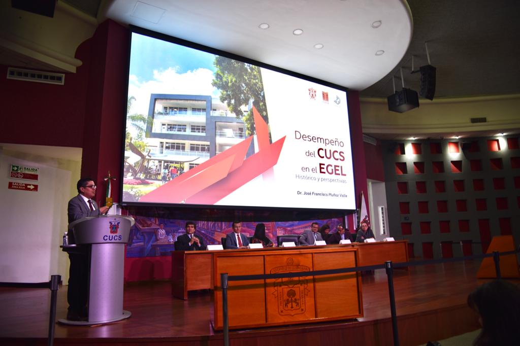 Rector del CUCS al micrófono en el pódium, toma abierta, al fondo una diapositiva en la pantalla y los miembros del presídium