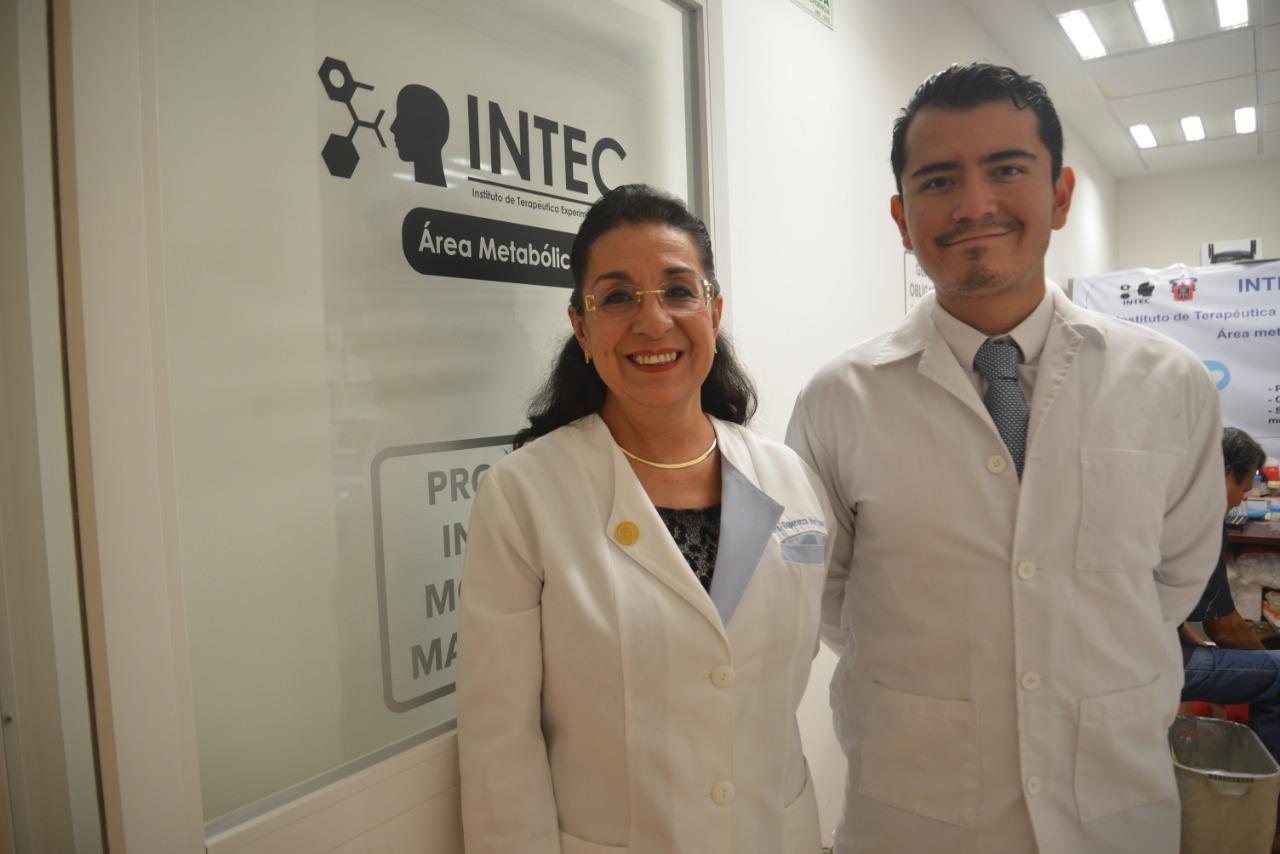 Dra. Esperanza Martínez y Dr. Luis Gaytán, atrás el letrero de INTEC en la puerta