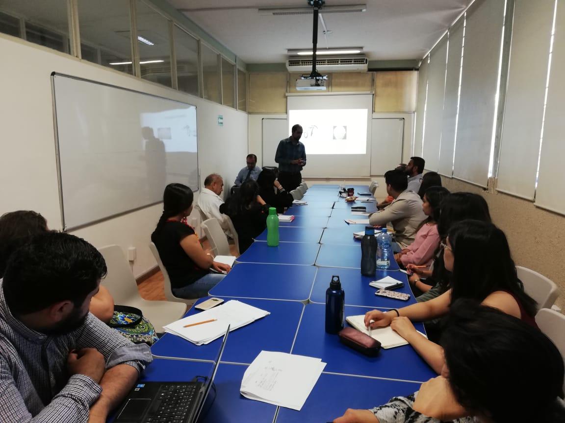 Foto general del grupo de asistentes, al fondo uno de los ponentes