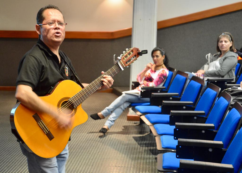 Cantante tocando la guitarra y cantando frente al grupo en el auditorio
