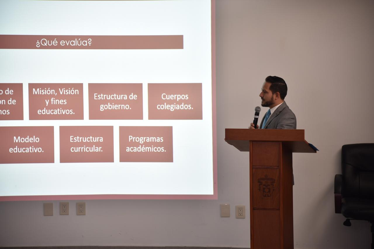 Coordinador de la Licenciatura en Medicina explicando una diapositiva de su presentación
