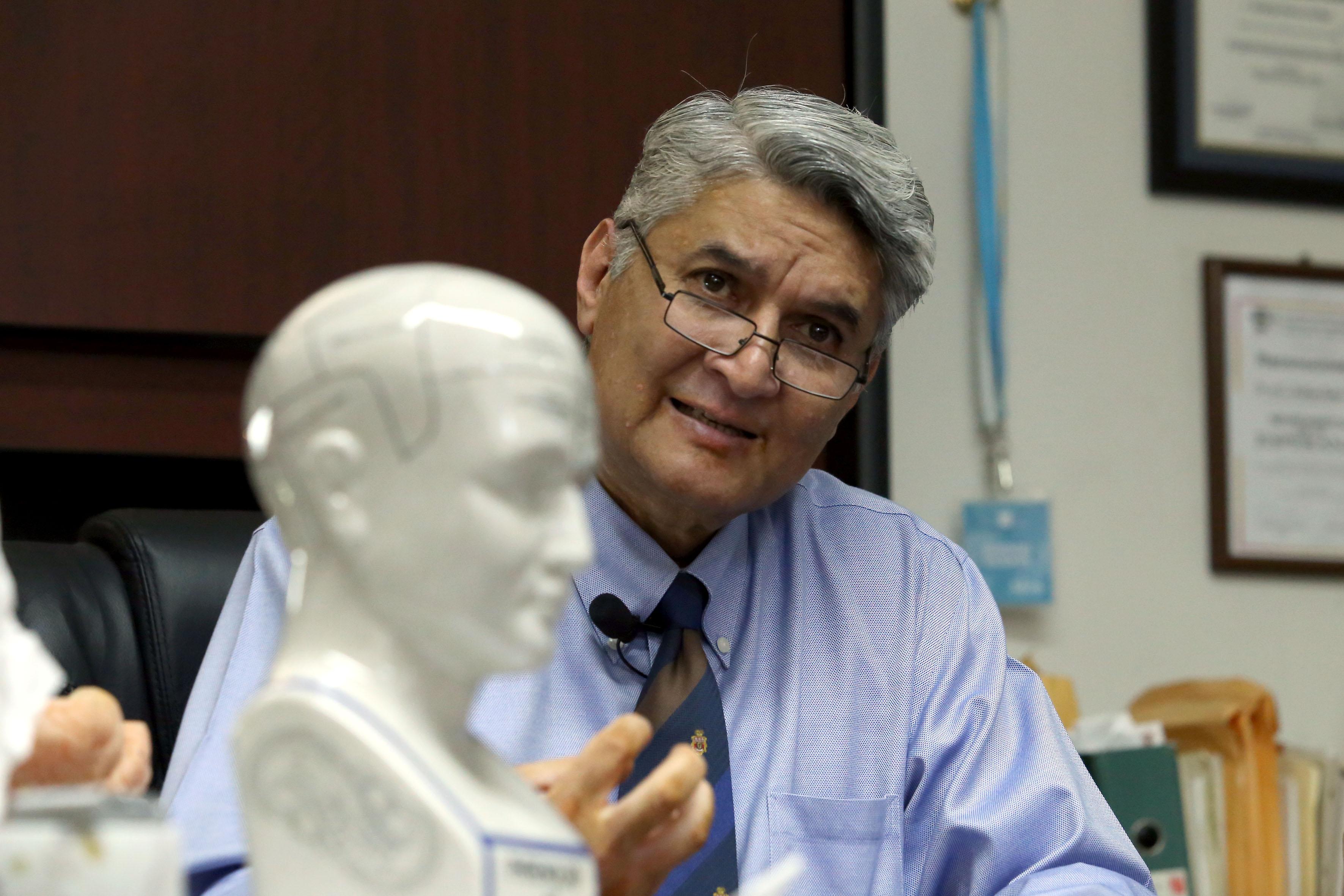 Imagen de la réplica de un cerebro, al fondo del Dr. Rodrigo RAmos