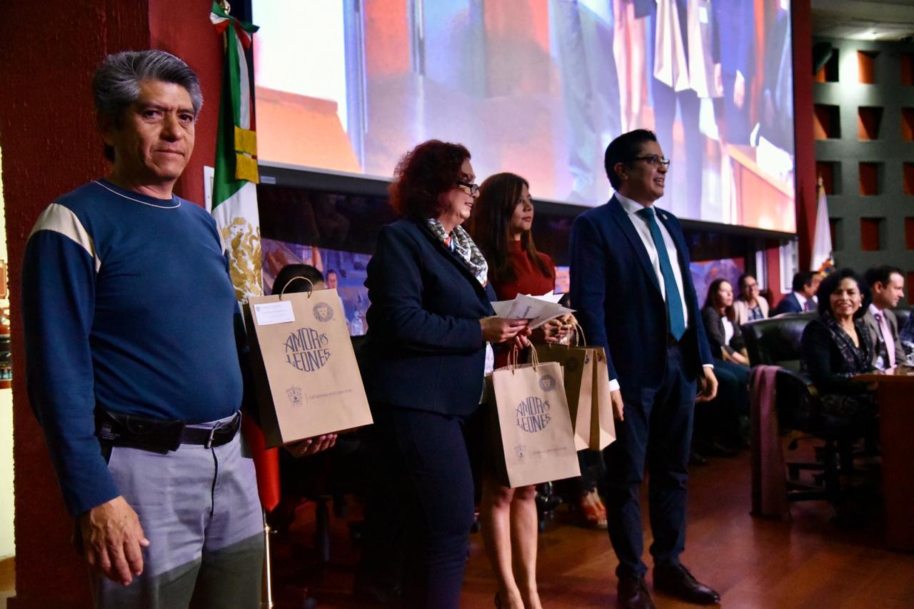 rector cucs posando para la foto con padres de familia que ganaron paquetes de libros