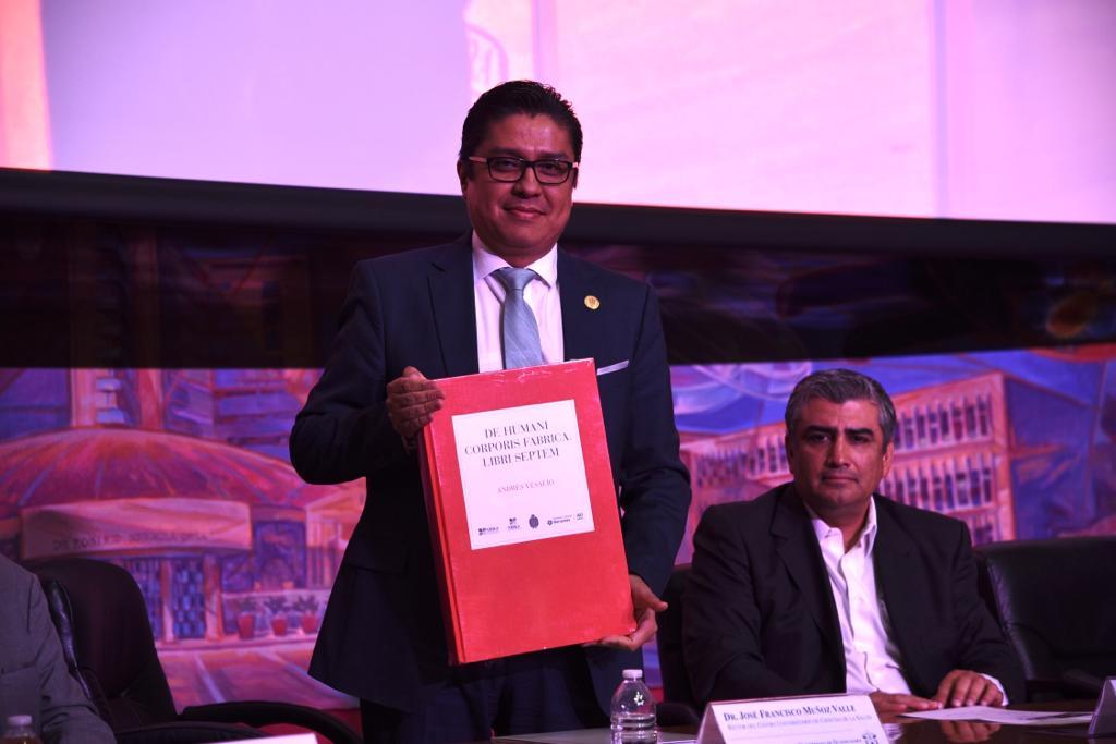 Rector del CUCS exhibiendo ejemplar de obra donada