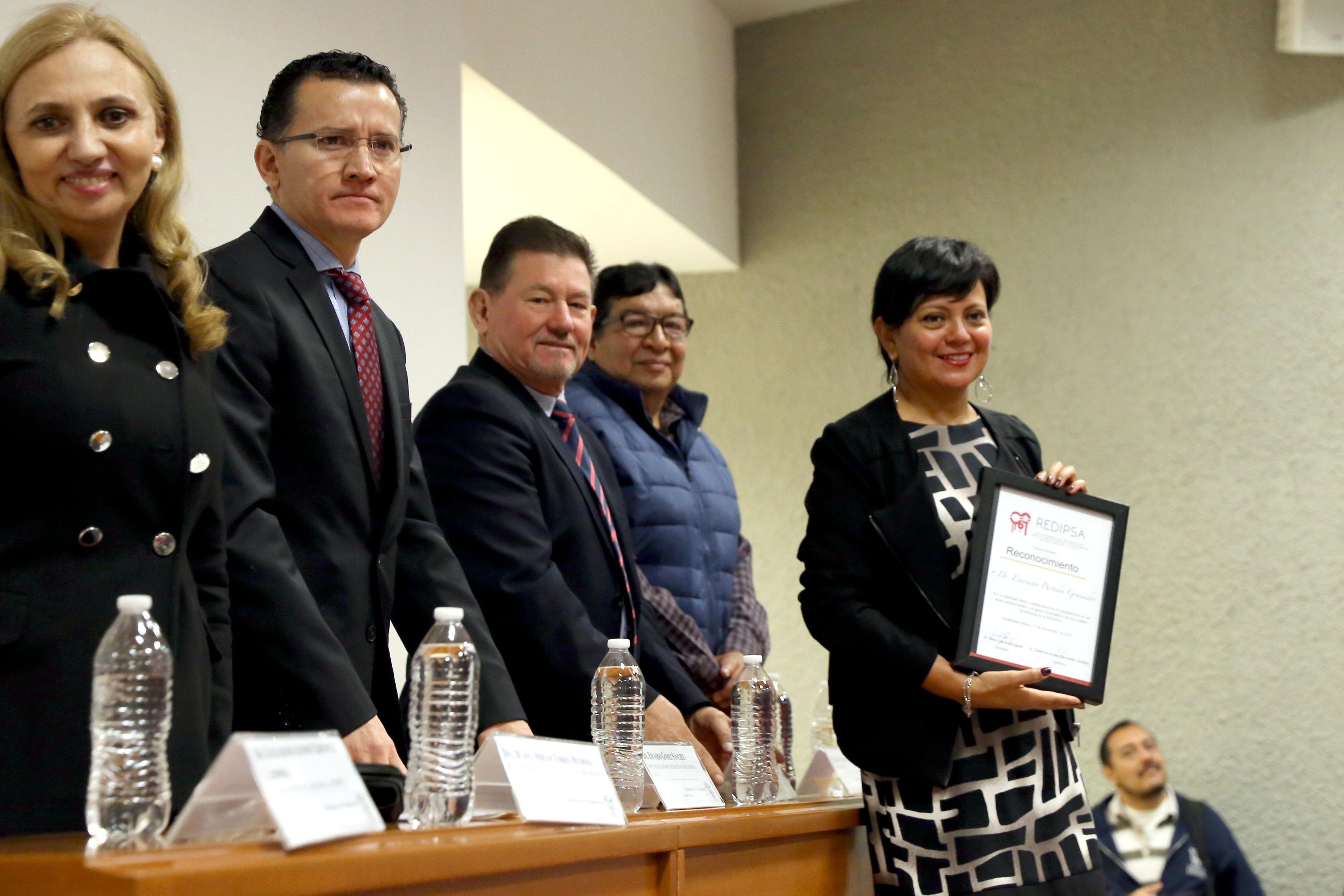 Miembros del presídium entregan reconocimiento a la Coordinación General de Comunicación Social
