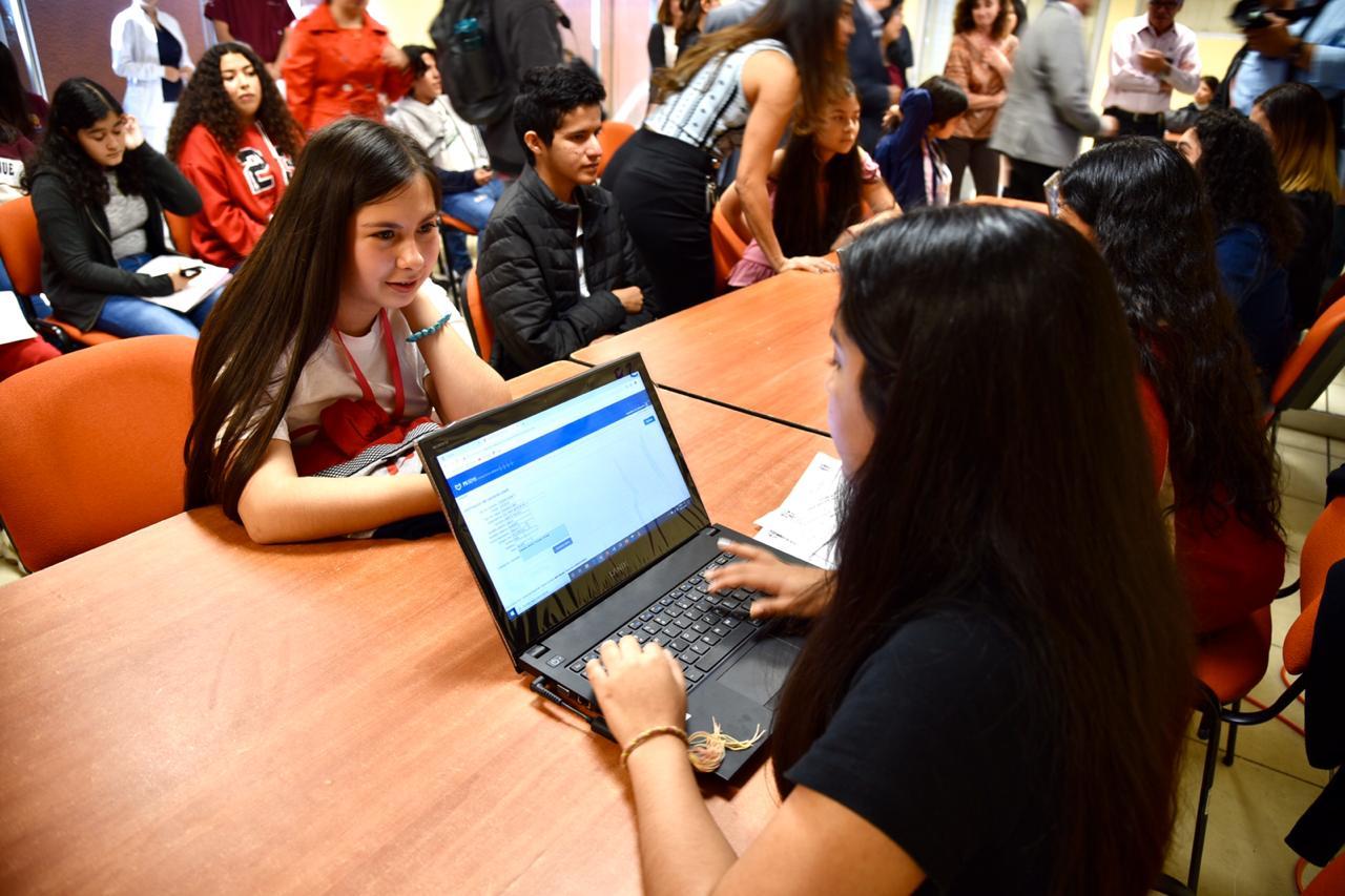 Pasante de medicina registrando datos en el sistema de una una alumna de la prepa