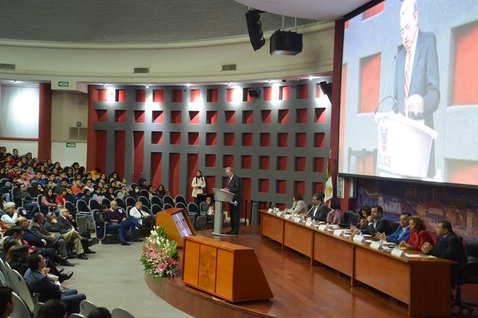 Miembros del presídium, al fondo el Dr. Zambrano dando mensaje de bienvenida