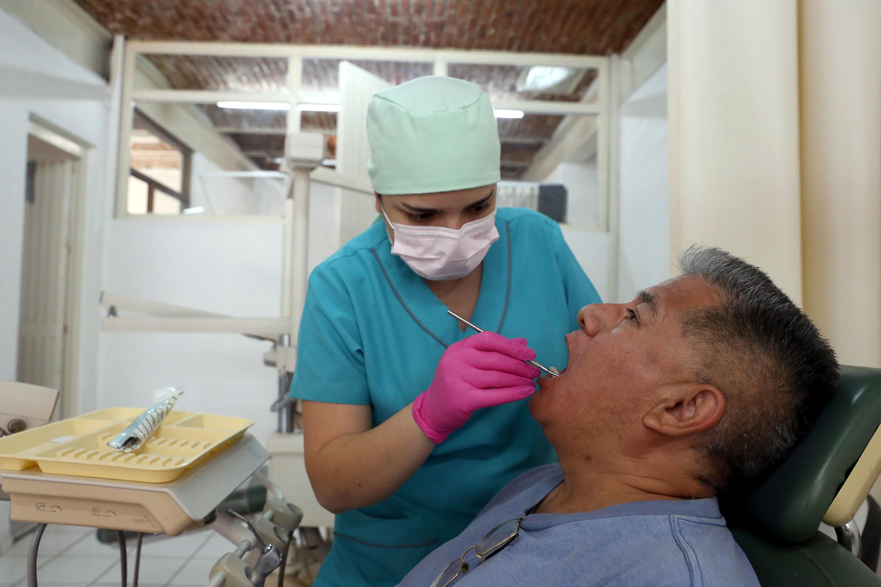 Pasante de Odontología atendiendo a un paciente